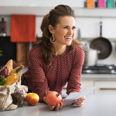 Woman in kitchen smiling holding fruit
