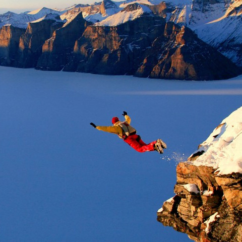 Man jumping off snowy cliff